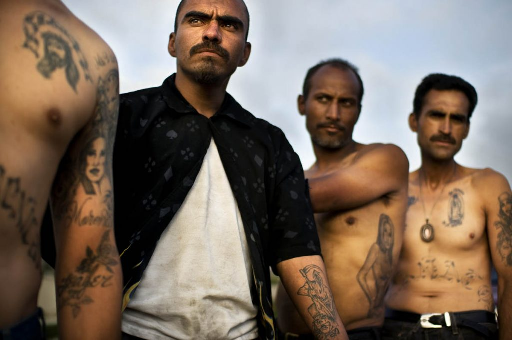"TIJUANA, BAJA CALIFORNIA, MX - JUNE 10 , 2009: Junkies with a tattoos, some of La Santa Muerte, hanging out on the ridge of the Rio Grande River basin on the the Tijuana side of the San Diego border region. It is common to see junkies in ""picaderos,"" or shooting galleries, shooting heroin along the border separating Mexico and the U.S., uninterrupted by nearby border patrol agents or Mexican police. Tijuana, a city of 1.3 million, has the highest prevalence of drug use in Mexico. The more than 2,000 mile border separating Mexico and the U.S forms the most extensive land frontier separating a developed and developing country. (Photo by Shaul Schwarz Reportage by Getty Images for National Geographic)"